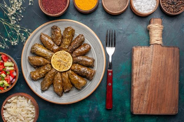 Vista dall'alto foglia dolma farina di carne orientale arrotolata all'interno di foglie verdi con verdure a fette e condimenti sulla scrivania blu cena a base di carne piatto pasto orientale