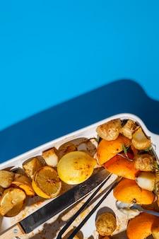Вид сверху остатки запеченной еды в подносе и тени