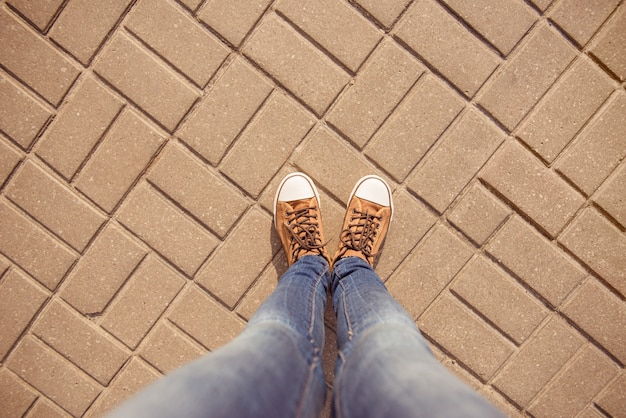 Top view of legs of girl in gumshoes and jeans on pavement