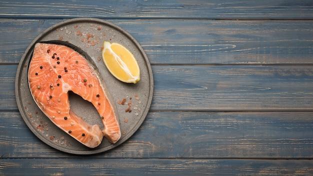 Вид сверху лимон и стейк из лосося на подносе с копией пространства