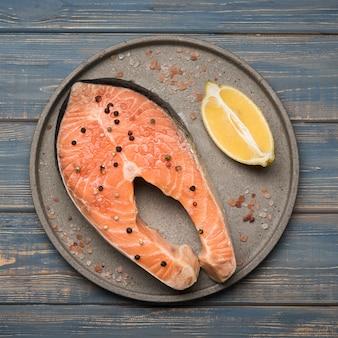 Вид сверху лимон и стейк из лосося на подносе