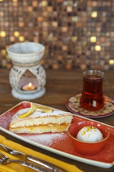 Top view of lemon cake with vanilla ice cream served with tea