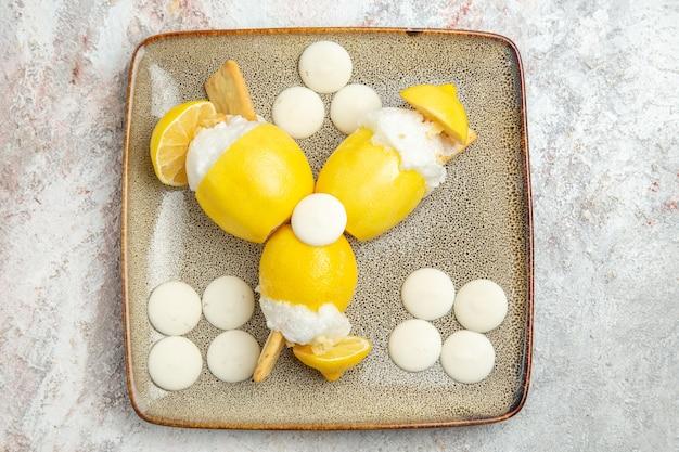 白いテーブルの上の白いキャンディーとレモンカクテルの上面図フルーツドリンクカクテルジュース