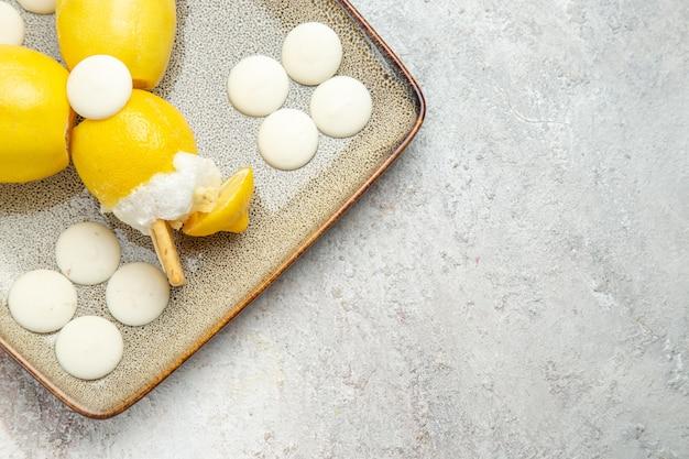 Vista dall'alto cocktail al limone con caramelle bianche su succo di cocktail bevanda di frutta pavimento bianco