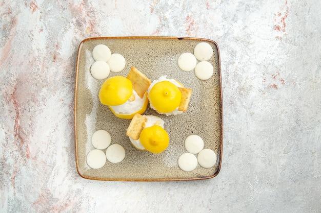 Vista dall'alto cocktail al limone con caramelle bianche sul cocktail di succo di agrumi tavolo bianco