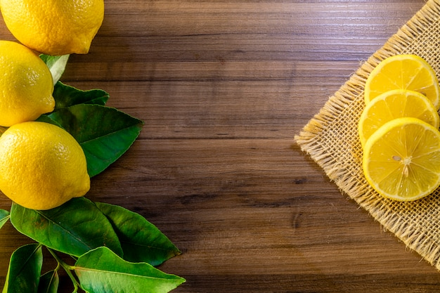 Top view of lemon and green leaves on wooden surface