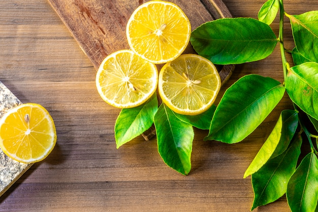 Top view of lemon and green leaves on wooden table