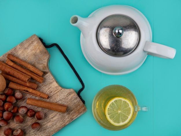 Top view of lemon juice with lemon slice in glass cup and nuts cinnamon walnut on cutting board with teapot on blue background