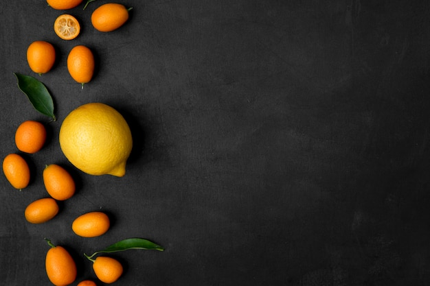 Top view of lemon and kumquats on left side on black surface