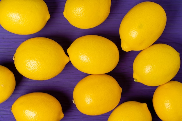 Top view of lemon on purple wooden background