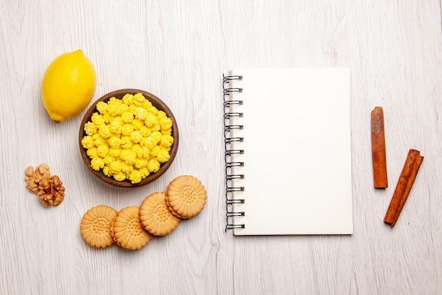 Taccuino bianco al limone e dolci con vista dall'alto accanto ai biscotti con bastoncini di cannella e ciotola di caramelle noci e limone sul tavolo bianco