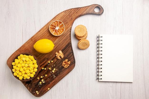 Vista dall'alto taccuino bianco limone e dolci accanto ai biscotti e ciotola di caramelle noci e limone sul tagliere sul tavolo bianco