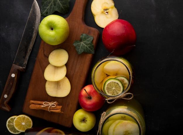 Вид сверху лимонного чая с лаймово-зеленым яблочным плющом, листьями красного яблока и корицы на доске