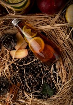 Vista dall'alto tè al limone con lime affettato mela rossa cannella e cono di abete sulla paglia