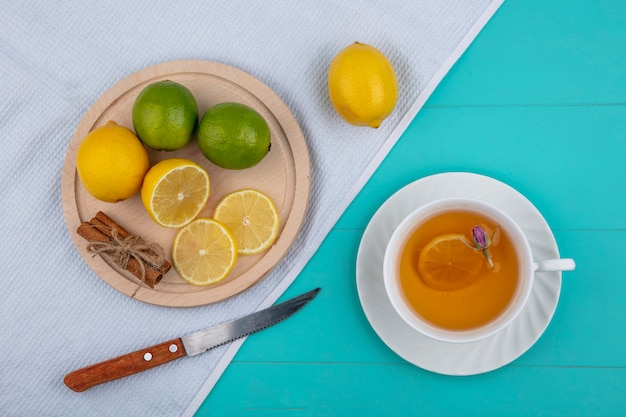 Top view lemon with lime on a tray with cinnamon a knife and a cup of tea on a white towel on a light blue background
