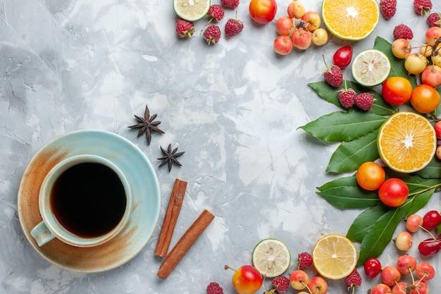 Вид сверху лимоны и вишни свежие фрукты с чаем корицей на светлом столе фрукты свежие спелые спелые