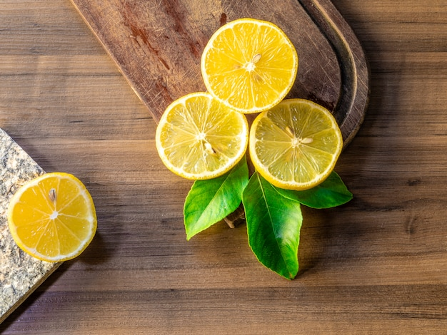 Top view of lemons and green leaves on wooden surface