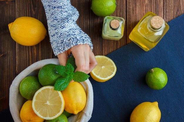 Лимоны в корзине с синей тканью, руки, держащие листья на деревянной поверхности. вертикальное пространство для текста