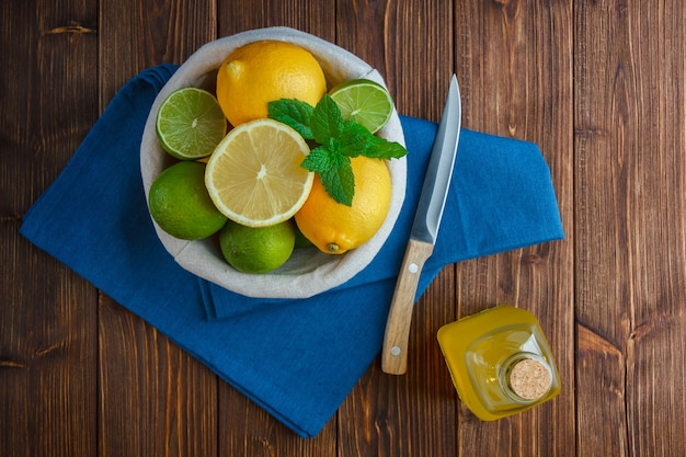 青い布、木製のナイフ、木製の表面にジュースのボトルとバスケットのトップビューレモン。