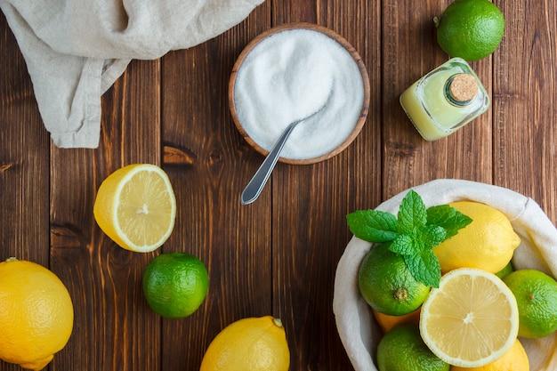 Вид сверху лимоны в корзине с белой тканью, миской соли, половиной лимона на деревянной поверхности. вертикальный