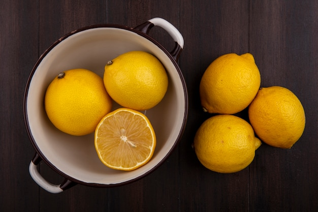 木製の背景に白い鍋のトップビューレモン