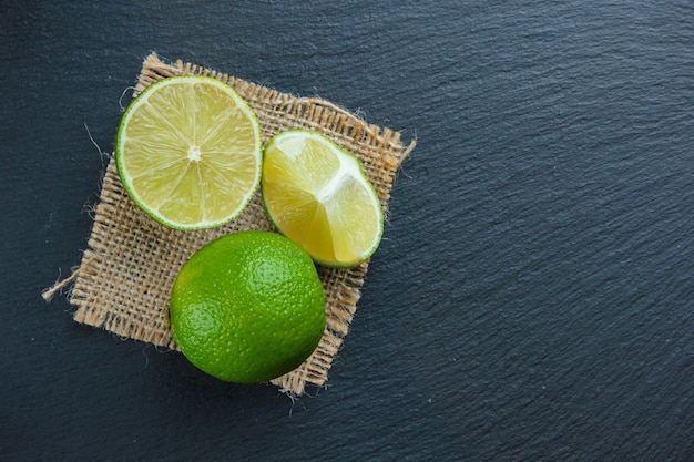 Top view lemons on piece of sack on dark stone background. vertical copy space for text