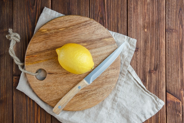 Top view lemons with lemon on cutting board on wooden surface. vertical