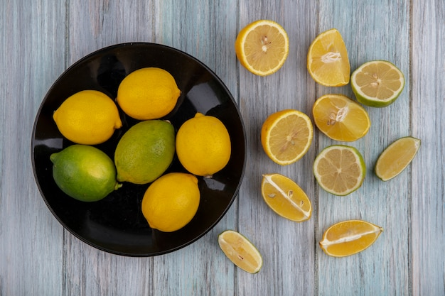 Top view lemons with lime on a black plate with wedges on a gray background