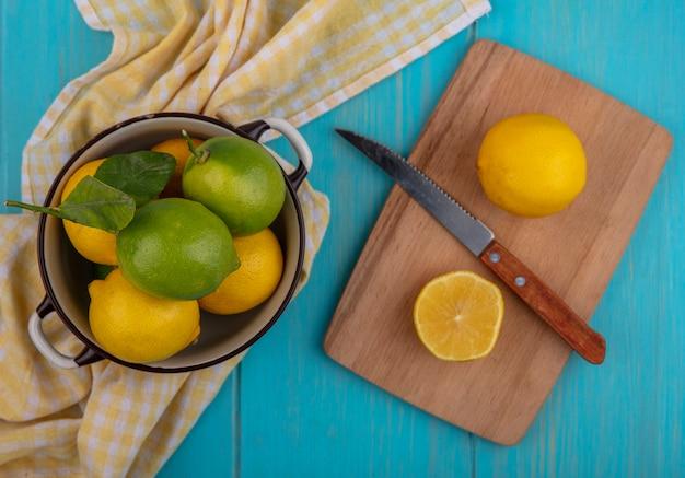 Vista dall'alto di limoni con lime in una casseruola con un coltello su un tagliere e un asciugamano a scacchi giallo su sfondo turchese