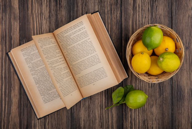 Top view lemons with limes in basket with open book on wooden background