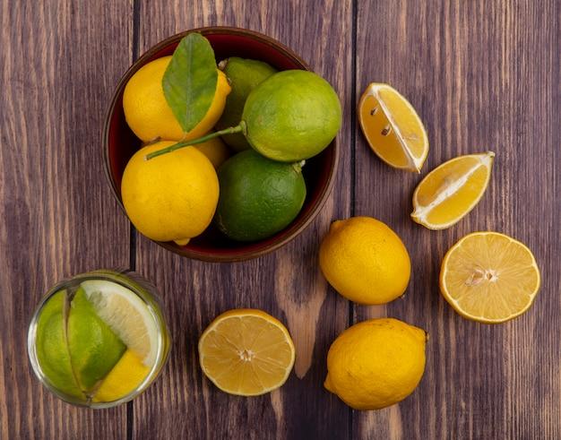 Limoni vista dall'alto con limette in ciotola e bicchiere di acqua detox su fondo di legno