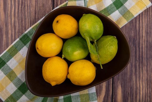 木の背景に黄緑色の市松模様のタオルの上のボウルにライムとレモンの上面図