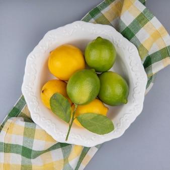 Лимоны с лаймами в тарелке на желтом клетчатом полотенце на сером фоне, вид сверху