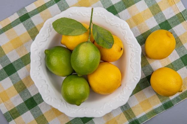 Лимоны с лаймом в тарелке на желтом клетчатом полотенце, вид сверху