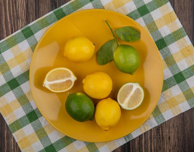 Limoni vista dall'alto con lime su un piatto giallo su un asciugamano a scacchi giallo-verde