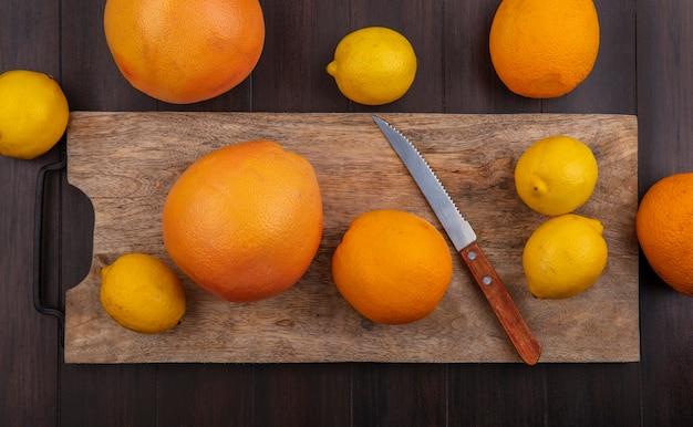 Limoni vista dall'alto con arance e pompelmo su un tagliere con un coltello su uno sfondo di legno