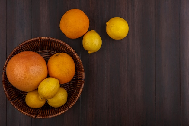Limoni vista dall'alto con arance e pompelmi con cesto su fondo in legno