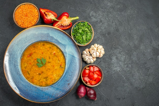 Vista dall'alto della zuppa di lenticchie lenticchie erbe spezie verdure pomodori cipolla ciotola di zuppa di lenticchie