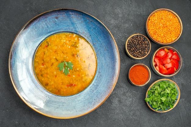 Vista dall'alto zuppa di lenticchie zuppa di lenticchie spezie erbe pomodori lenticchie sul tavolo scuro