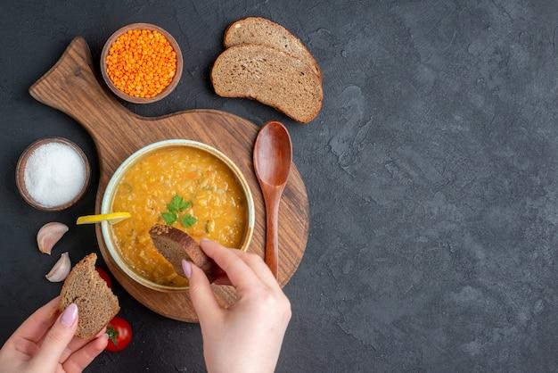 暗い表面に暗いパンと一緒に食べる女性と一緒に上面図レンズ豆のスープ