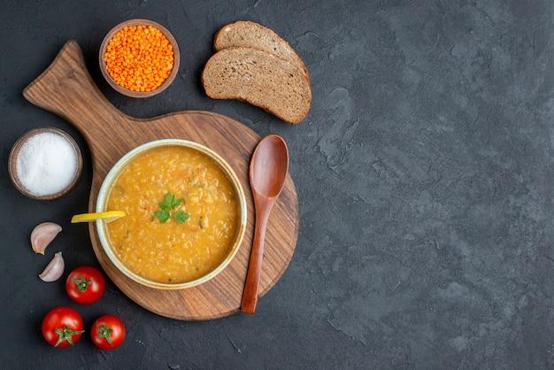 暗い表面に塩の生レンズ豆と暗いパンのパンが入った上面図レンズ豆のスープ