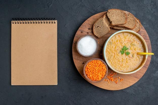 Vista dall'alto zuppa di lenticchie con lenticchie crude sale e pagnotte di pane scuro su superficie scura
