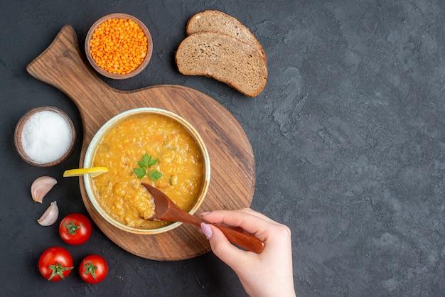 어두운 표면에 소금 토마토와 어두운 빵 덩어리가 들어간 상위 뷰 렌즈 콩 수프