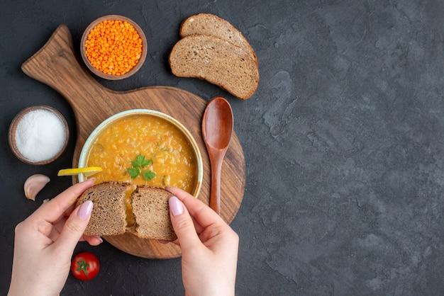 暗い表面に塩トマトと暗いパンのパンが付いた上面レンズ豆のスープ