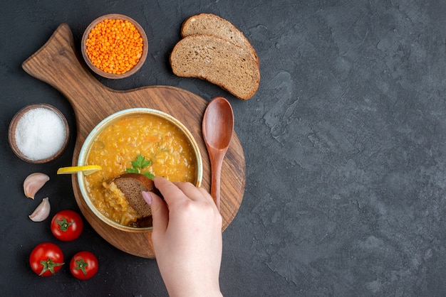 Vista dall'alto zuppa di lenticchie con pomodori al sale e pagnotte di pane scuro su superficie scura