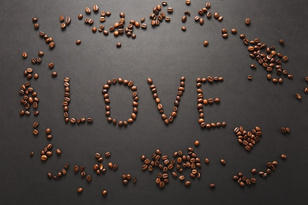 Top view of letter love, word made from coffee beans on black background for design