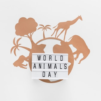 Top view of light box with paper planet and animals for animal day