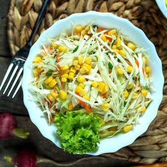 Вид сверху светлый салат из капусты с кукурузным салатом и редисом