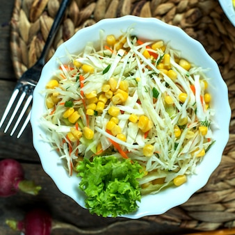 Insalata di cavolo leggera vista dall'alto con lattuga di mais e ravanello