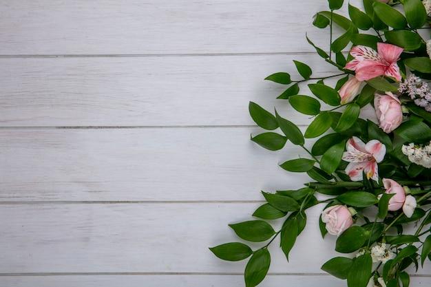 Vista dall'alto di fiori rosa chiaro con foglie su una superficie grigia
